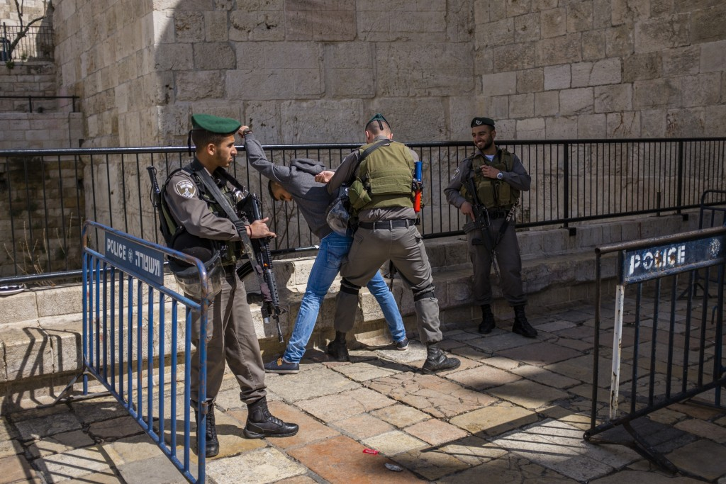Israeli Soldiers check an Arab civilian in front of Shaar Shchem in Yerushalayim. (Corinna Kern/Flash90)