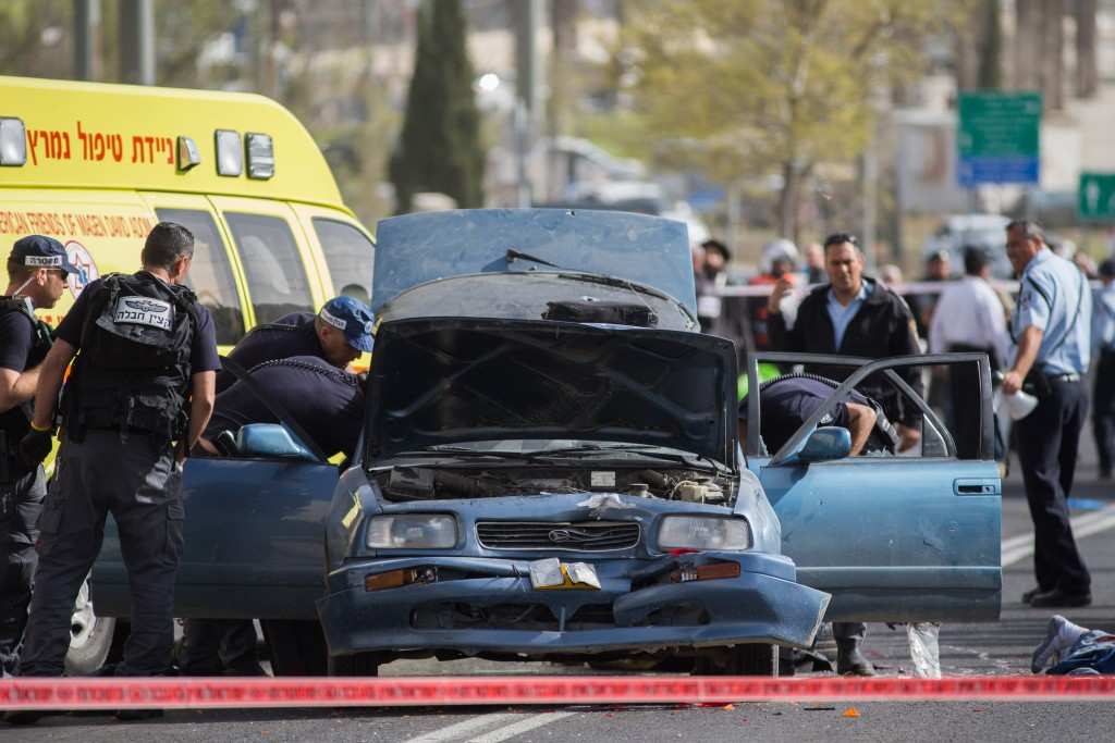 Israeli security at the scene where a man was seriously injured when a Palestinian terrorist drove his vehicle into pedestrians, near Shaar Shchem in Yerushalayim. The terrorist was shot at the scene. March 09, 2016. (Yonatan Sindel/Flash90)