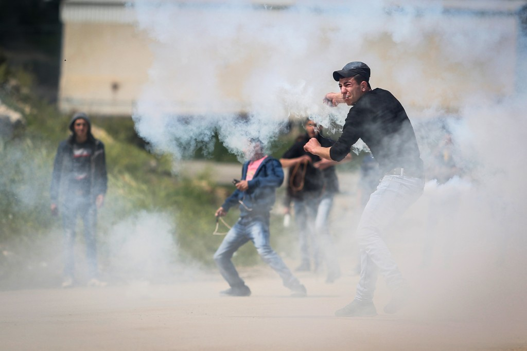 Palestinians protest in front of Israeli security forces as they mark Land Day outside the compound of the Israeli-run Ofer prison near Betunia on March 30, 2016. (Flash90)