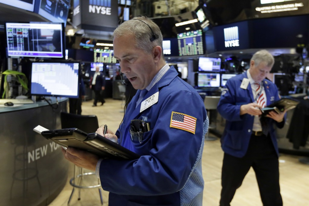 Trader Timothy Nick, left, works on the floor of the New York Stock Exchange on Friday. (AP Photo/Richard Drew)
