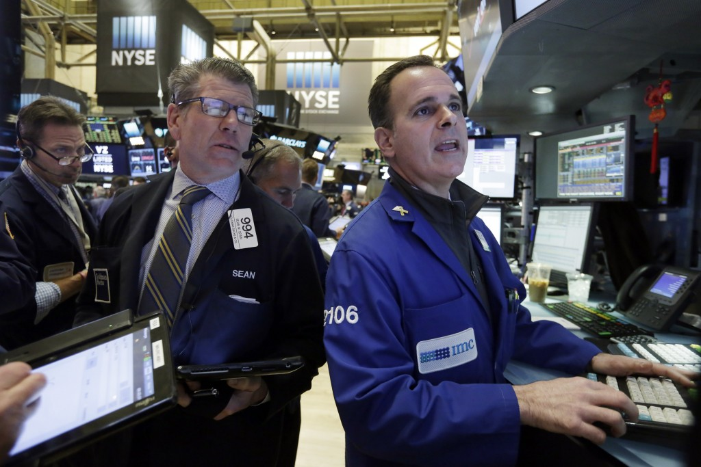 Trader Sean Spain, CENTER, and specialist John Alatzas, right, work on the floor of the New York Stock Exchange on Wednesday. (AP Photo/Richard Drew)