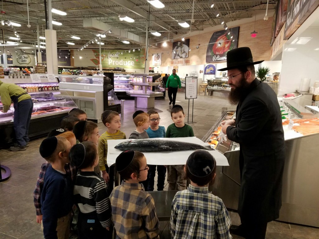 Rabbi Yochonon Perlowitz, pre-1A rebbi at Yeshivah Stolin Karlin in Lakewood, on Wednesday at Gourmet Glatt teaches his class the simanim of a kosher fish, a subject of this week's parashah. (Yeshivah Stolin Karlin)