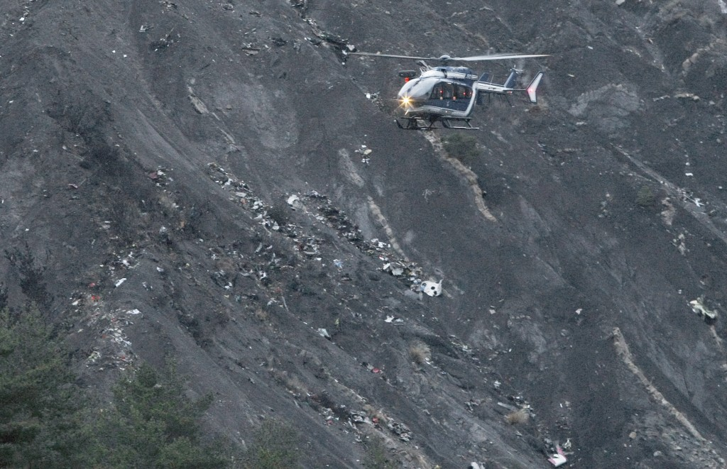 FILE - In this March 24, 2015 file picture a recue helicopter flies over debris of the Germanwings passenger jet, scattered on the mountain side, near Seyne les Alpes, French Alps and killing all 150 people on board. France's air accident investigation agency releases report into the March 2015 crash of the Germanwings jet on March 13, 2016 . (AP Photo/Claude Paris,file)