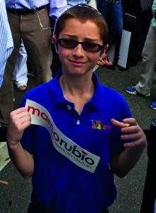 A boy holding a bumper sticker from the Rubio campaign.