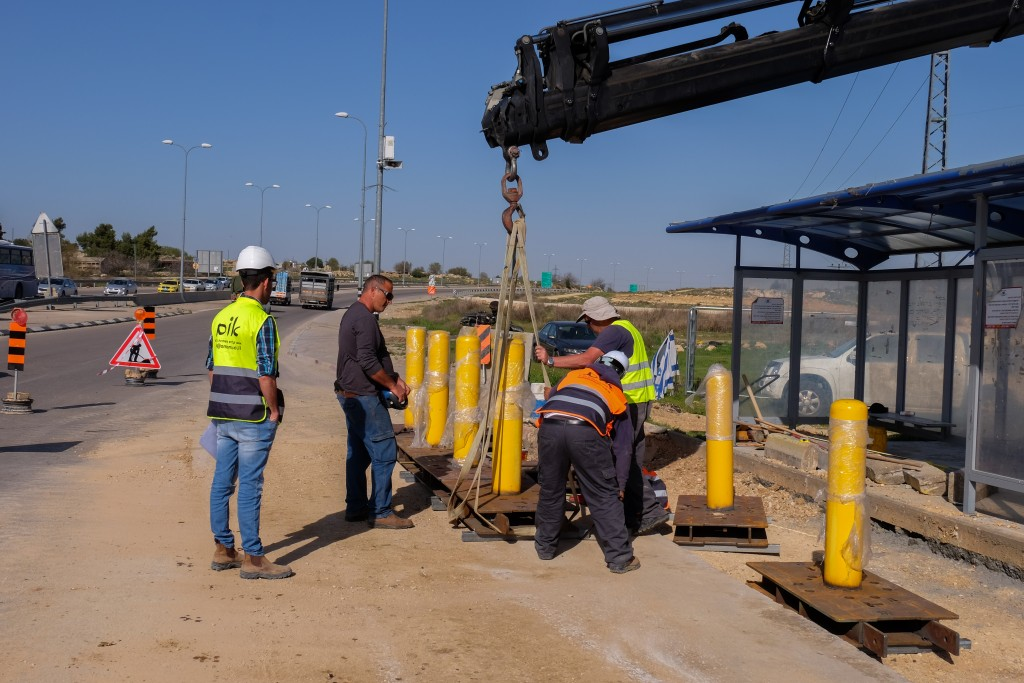 Workers installing barriers at a bus stop in the Gush Etzion junction on Monday. (Gershon Elinson/Flash90)