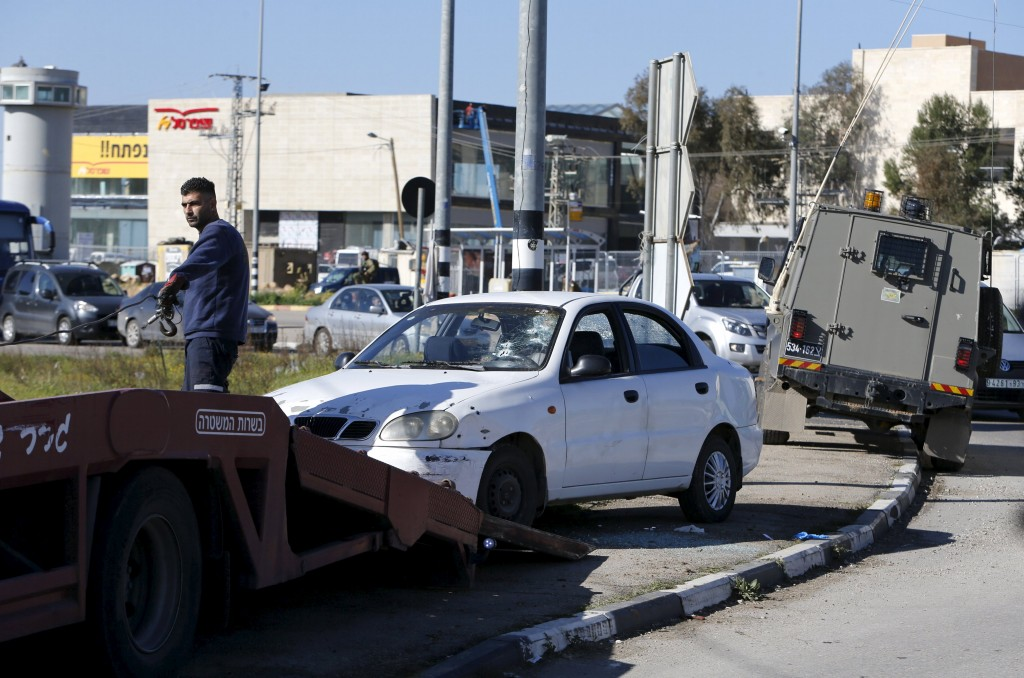 A car used by a Palestinian woman who, the Israeli military said, rammed it into an Israeli soldier before she was shot dead by the Israeli troops, is removed from the scene at a main junction near the Israeli settlement bloc, Gush Etzion in the West Bank March 4, 2016. REUTERS/Mussa Qawasma