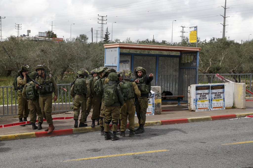 Israeli soldiers gather near the scene where the Israeli military said two Palestinians stabbed and wounded an Israeli woman and were then shot and killed outside the Jewish settlement of Ariel in the occupied West Bank March 17, 2016. REUTERS/Baz Ratner