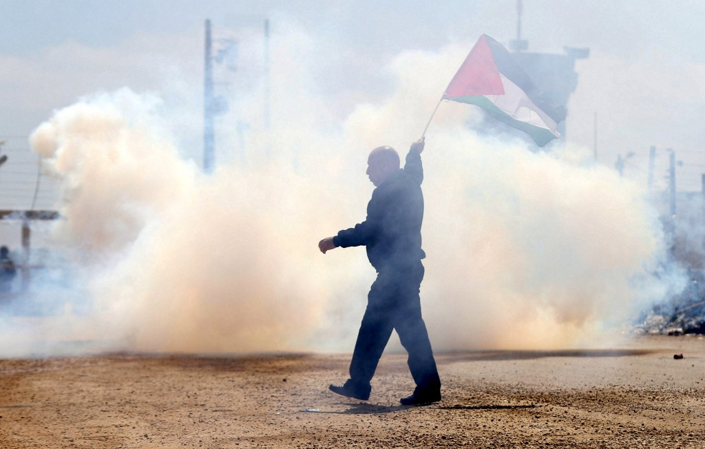 A Palestinian protester holds a Palestinian flag as he reacts to tear gas fired by Israeli troops during clashes at a protest marking Land Day, near Israel's Ofer Prison near the West Bank city of Ramallah March 30, 2016. March 30 marks Land Day, the annual commemoration of protests in 1976 against Israel's appropriation of Arab-owned land in the Galilee. REUTERS/Mohamad Torokman