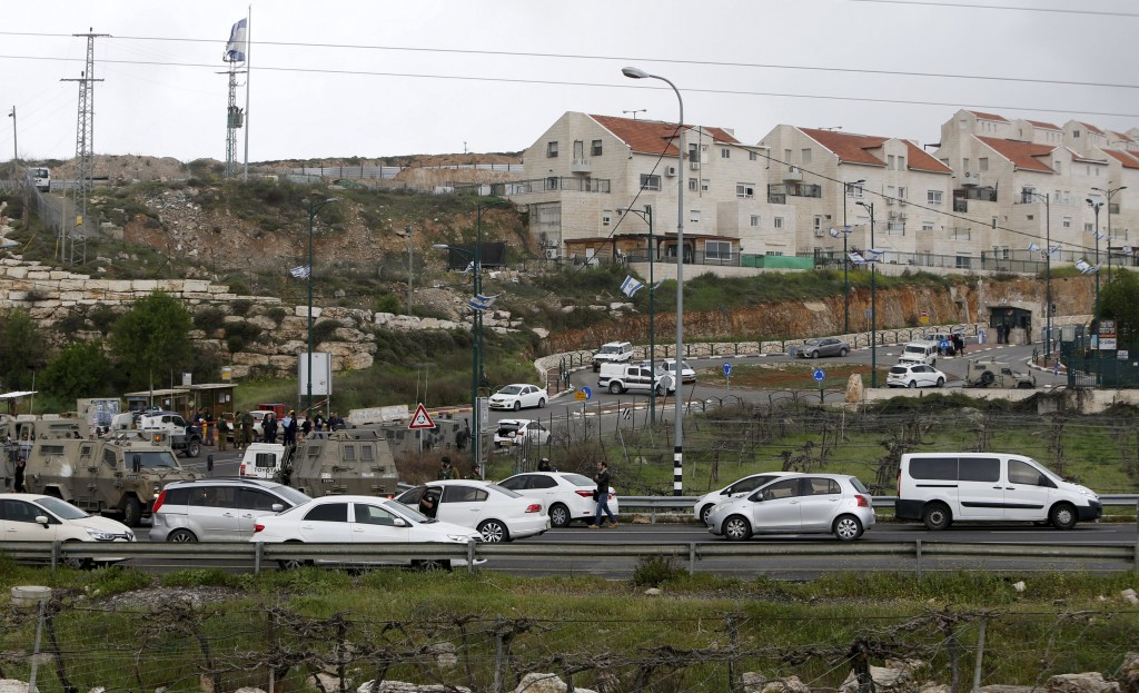 Israeli security forces gather at the scene of what the Israeli military said were back-to-back gun and car-ramming attacks by Palestinians, near the Jewish settlement of Kiryat Arba near the West Bank city of Hebron March 14, 2016. Three Palestinians carried out back-to-back gun and car-ramming attacks on Israelis near a Jewish settlement in the occupied West Bank on Monday and were shot dead by the army, it said. REUTERS/Mussa Qawasma