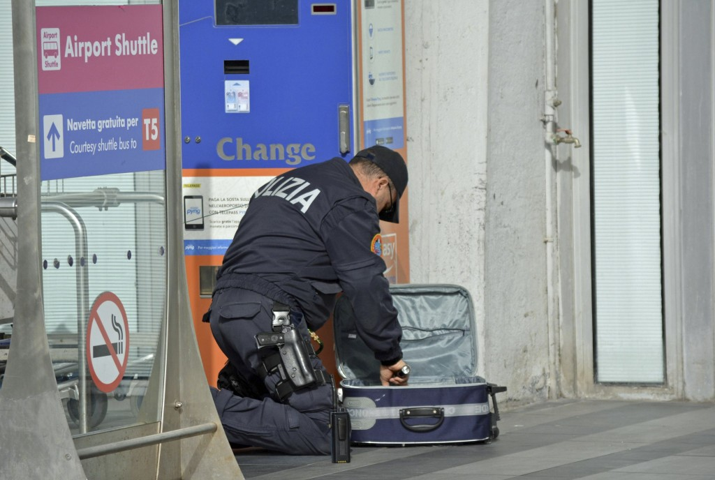 A police officer searches through a suitcase at Fiumicino airport, near Rome, Tuesday, March 22, 2016. The Italian Interior Ministry announced heightened security measures at major Italian airports following explosions at the Brussels airport and the subway system earlier Tuesday. (Telenews/ANSA via AP) ITALY OUT