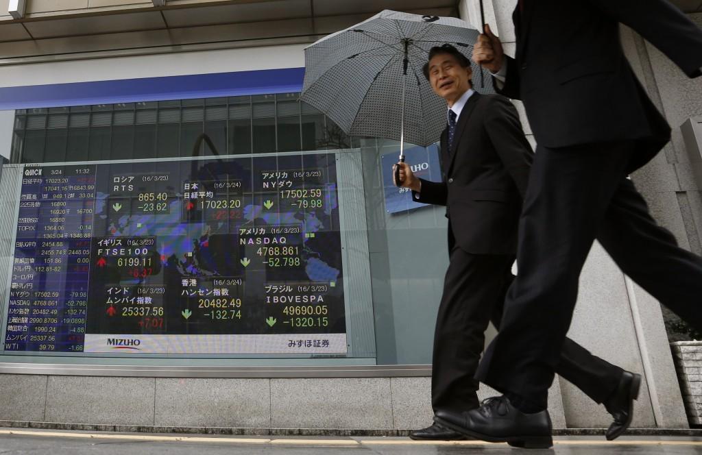 Pedestrians walk past an electronic stock board showing the global financial index at a securities firm in Tokyo on Thursday. (AP Photo/Shuji Kajiyama)