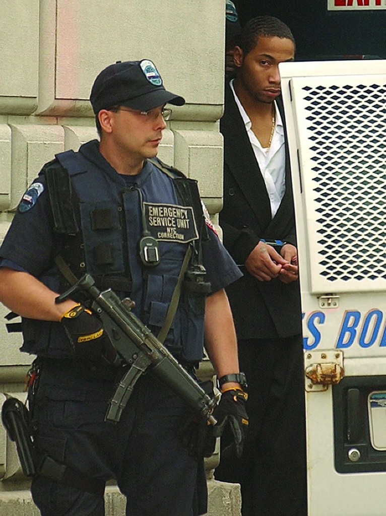 FILE - In this July 30, 2003, file photo, Ronell Wilson is escorted past a heavily armed corrections officer after appearing in court to face charges in the shooting death of two undercover police officers on the Staten Island, N.Y. On Tuesday, March 15, 2016, a federal judge ruled that Wilson is intellectually disabled and vacated the order sentencing him to death. (AP Photo/Ed Betz, File)