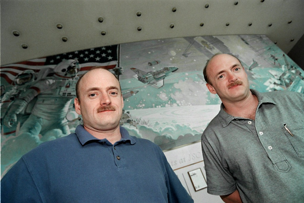 FILE - In this March 25, 1999 file photo, NASA astronauts Scott, left, and Mark Kelly, who are twins, pose for a picture in front of a mural at Johnson Space Center in Houston. On Friday, March 11, 2016, NASA announced Kelly's retirement, which begins April 1. The 52-year-old Kelly holds the American record for most time in space: 520 days. (AP Photo/Michael Stravato)