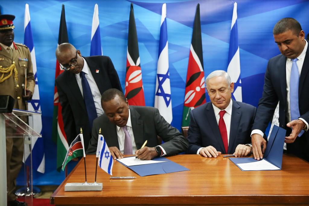 Israeli Prime Minister Binyamin Netanyahu and Kenyan President Uhuru Kenyatta signing joint agreements, at PM Netanyahu's office in Yerushalayim, February 23. (Ohad Zwigenberg/POOL)