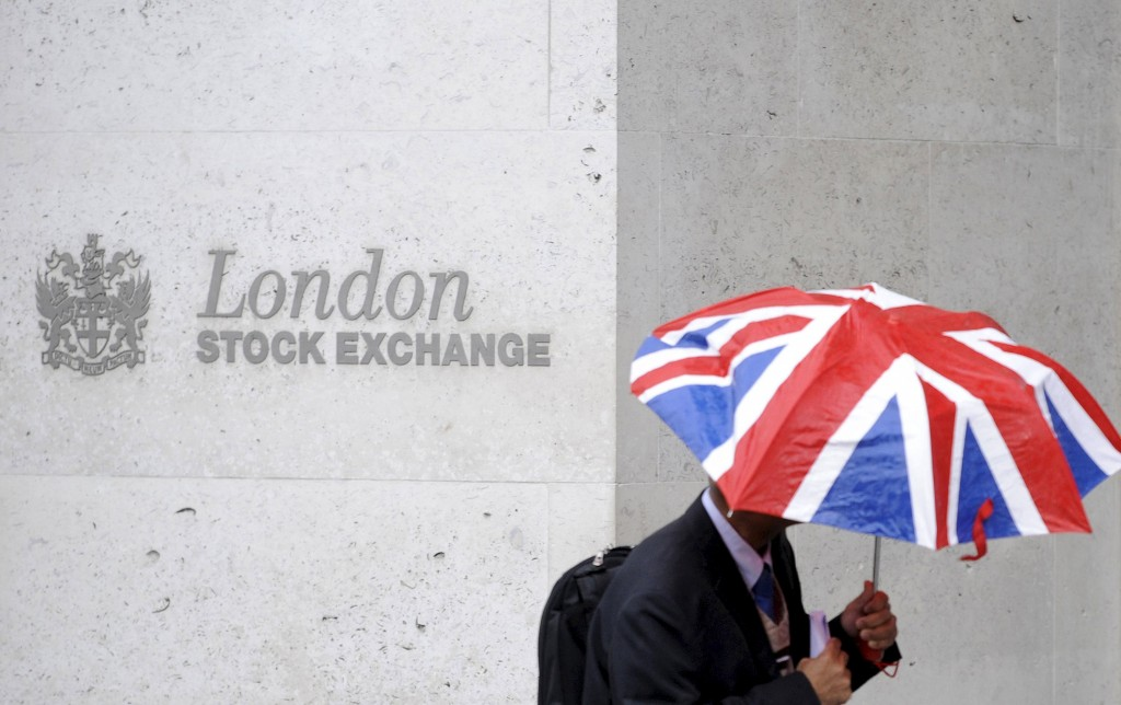 A worker shelters from the rain as he passes the London Stock Exchange in the City of London, Britain, in this October 1, 2008 file photo. Deutsche Boerse AG and London Stock Exchange Group Plc (LSEG) said they had reached a merger agreement and saw potential cost savings of 450 million euros ($499 million) per year for the combined company. REUTERS/Toby Melville/Files