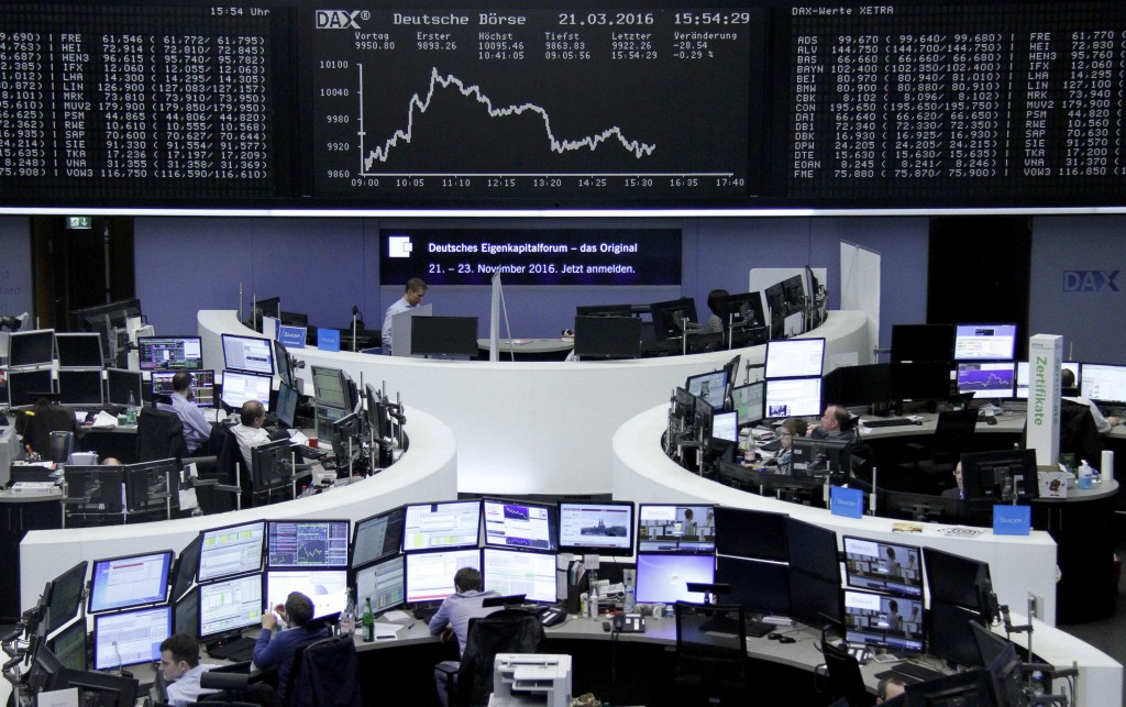 Traders work at their desks in front of the German share price index, DAX board, at the stock exchange in Frankfurt, Germany, March 21, 2016. REUTERS/Staff/Remote