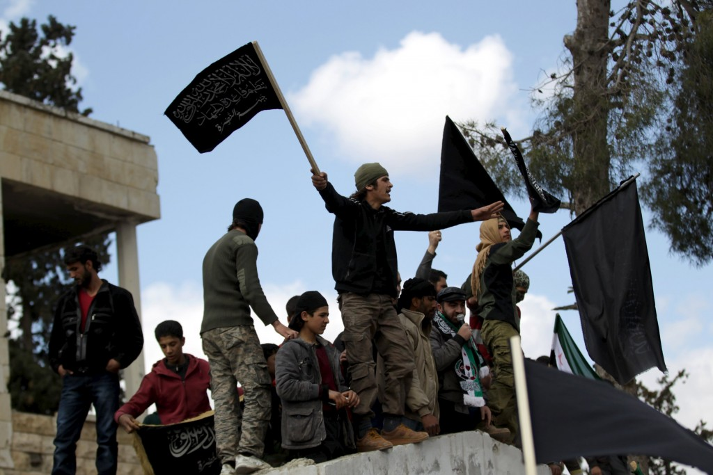 Protesters carry Nusra Front flags and shout slogans during an anti-government protest in the town of Marat Numan in Idlib province, Syria, March 11, 2016. REUTERS/Khalil Ashawi