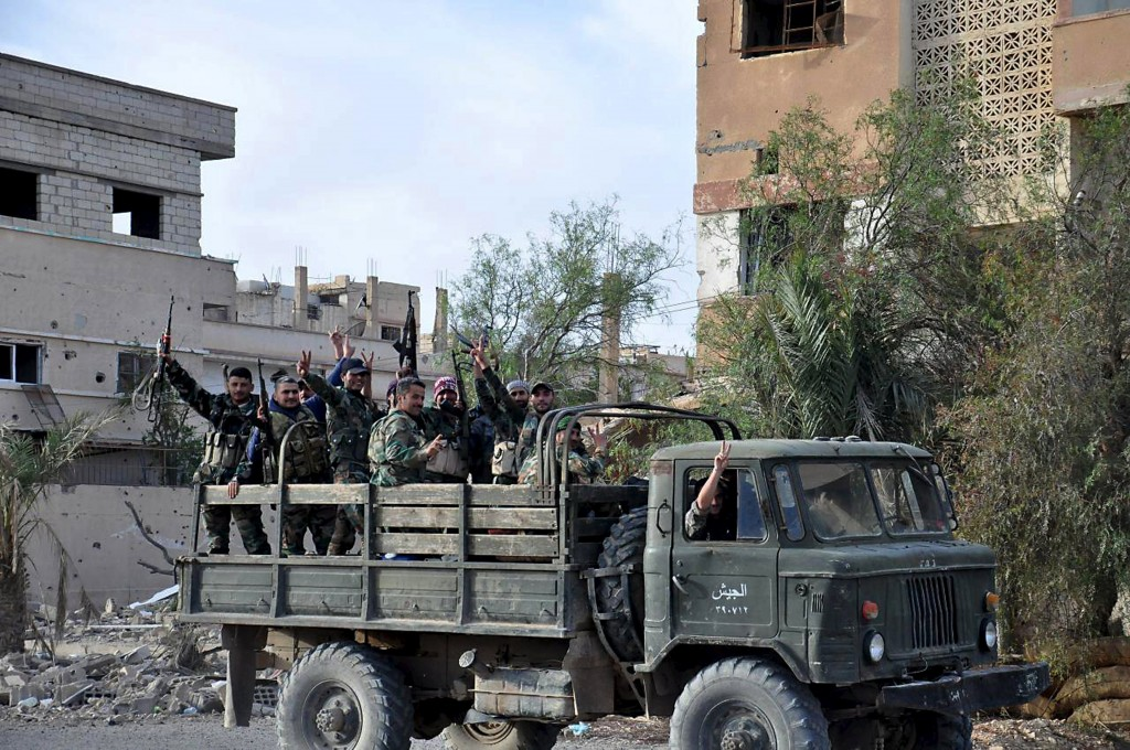 Forces loyal to Syria's President Bashar al-Assad flash victory signs while riding on the back of a military truck in Palmyra city, in Homs Governorate in this handout picture provided by SANA on March 27, 2016. REUTERS/SANA/Handout via Reuters ATTENTION EDITORS - THIS PICTURE WAS PROVIDED BY A THIRD PARTY. REUTERS IS UNABLE TO INDEPENDENTLY VERIFY THE AUTHENTICITY, CONTENT, LOCATION OR DATE OF THIS IMAGE. FOR EDITORIAL USE ONLY. NOT FOR SALE FOR MARKETING OR ADVERTISING CAMPAIGNS. THIS PICTURE IS DISTRIBUTED EXACTLY AS RECEIVED BY REUTERS, AS A SERVICE TO CLIENTS