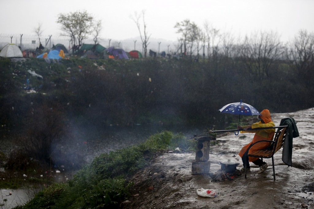 A migrant boy protects the food his family is cooking with an umbrella, during a heavy rainfall, at a makeshift camp on the Greek-Macedonian border, near the village of Idomeni, Greece March 12, 2016.  REUTERS/Stoyan Nenov