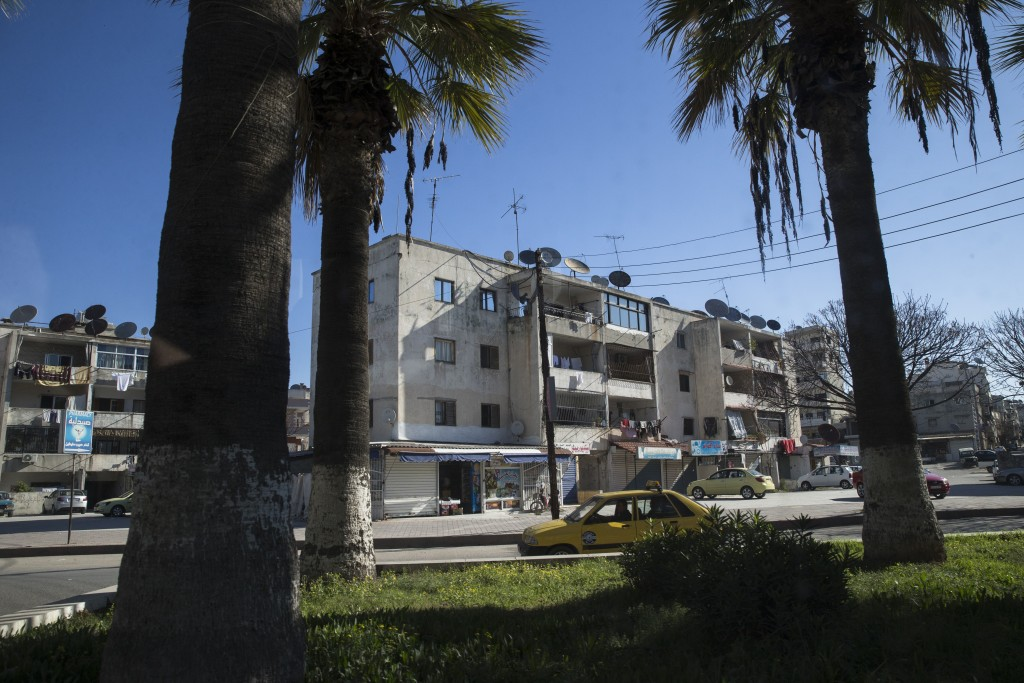 In this photo taken on Tuesday, March 1, 2016, a car passes on a street in Latakia, Syria. Associated Press spent five days traveling through the port of Latakia in Syria during the ceasefire. (AP Photo/Pavel Golovkin)