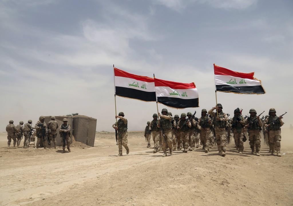 FILE - In this Wednesday, May 27, 2015, file photo, U.S. soldiers, left, participate in a training mission with Iraqi army soldiers outside Baghdad, Iraq. It will take many more months to prepare Iraq's still struggling military for a long-anticipated assault on the Islamic State group's biggest stronghold in the country, the city of Mosul, U.S. and Iraqi officials say _ and it may not even be possible to retake it this year, despite repeated vows by Prime Minister Haider al-Abadi. (AP Photo/Khalid Mohammed)