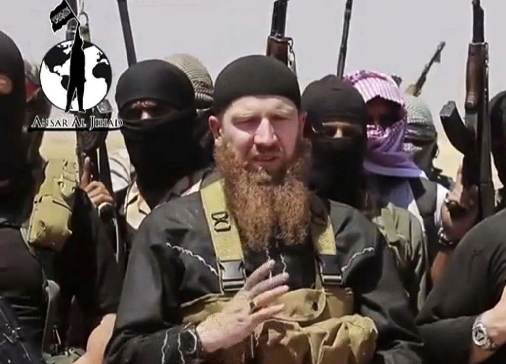 FILE - This image made from undated video posted during the weekend of June 28, 2014 on a social media account frequently used for communications by the Islamic State of Iraq and the Levant (ISIL), which has been verified and is consistent with other AP reporting, shows Omar al-Shishani standing next to the group's spokesman among a group of fighters as they declare the elimination of the border between Iraq and Syria. An Iraqi official and a Syrian activist say senior Islamic State group leader Al-Shishani died Monday, March 15, 2016 outside Raqqa, Syria. Shishani was injured in a U.S. airstrikes last week and subsequently died from his wounds, the senior Iraqi intelligence official and Rami Abdurrahman, of the Britain-based Syrian Observatory for Human Rights told the Associated Press. (AP Photo/militant social media account via AP video)