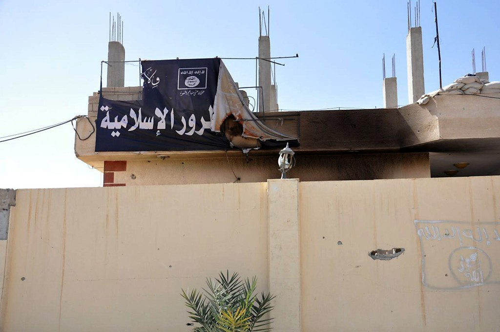 This photo released on Sunday March 27, 2016, by the Syrian official news agency SANA, shows a burned banner of the Islamic State group, in the ancient city of Palmyra, central Syria. The amount of destruction found inside the archaeological area in the historic town was similar to what experts have expected but the shock came Monday from inside the local museum where the extremists have caused wide damage demolishing invaluable statues that were torn to pieces. (SANA via AP)