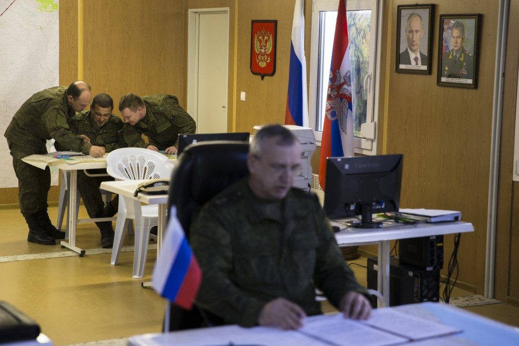 Russian officers talk over a map in the Russian military coordination center at Hemeimeem air base in Syria, Friday, March 4, 2016. The Russian military says it has been in regular contact with the U.S. counterparts on monitoring the Russian- and U.S.-brokered cease-fire has begun last weekend. (AP Photo/Pavel Golovkin)