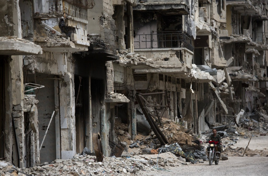 FILE - In this Thursday June 5, 2014 file photo, a man rides a motorcycle in a devastated part of Homs, Syria. (AP Photo/Dusan Vranic, File)