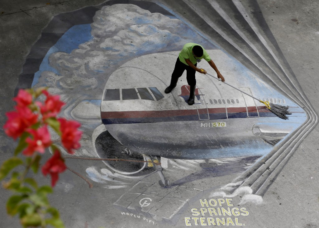"In this April 8, 2014 photo, a school utility worker mops a mural depicting the missing Malaysia Airlines Flight 370 at the Benigno ""Ninoy"" Aquino High School campus at Makati city east of Manila, Philippines. (AP Photo/Bullit Marquez, File)"