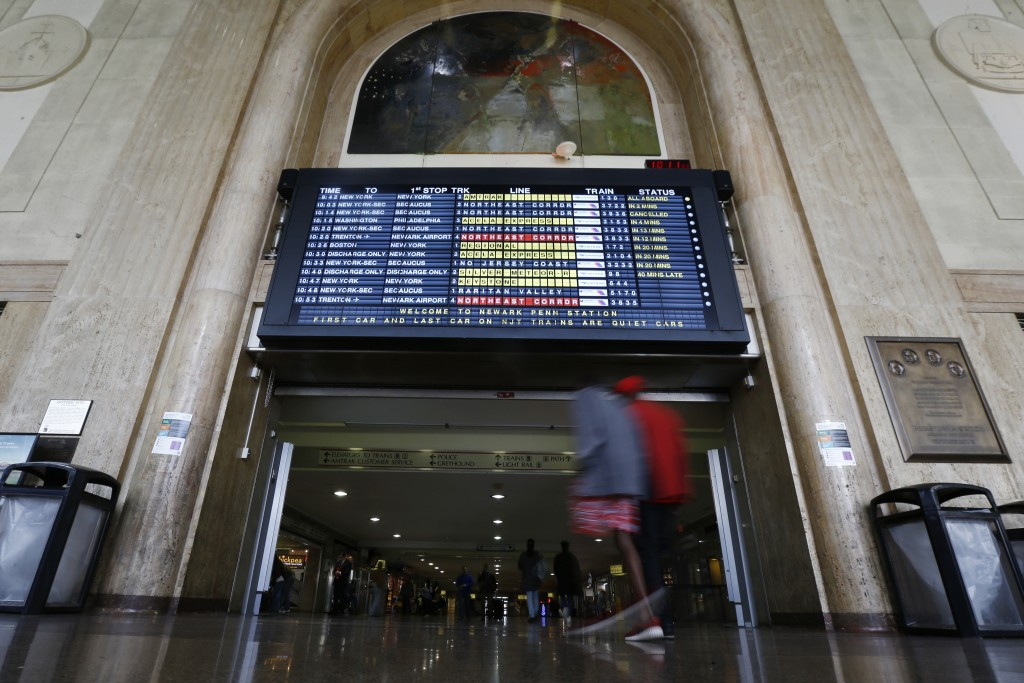 Train schedule is seen as commuters walk at Newark Penn Station, Friday, March 11, 2016, in Newark, N.J. More than 100,000 commuters use NJ Transit to get into New York City. The transit agency had said its contingency plan using extra buses would only be able to accommodate about 40,000 riders. NJ Transit had estimated that a one-hour commute by train would more than double. (AP Photo/Julio Cortez)