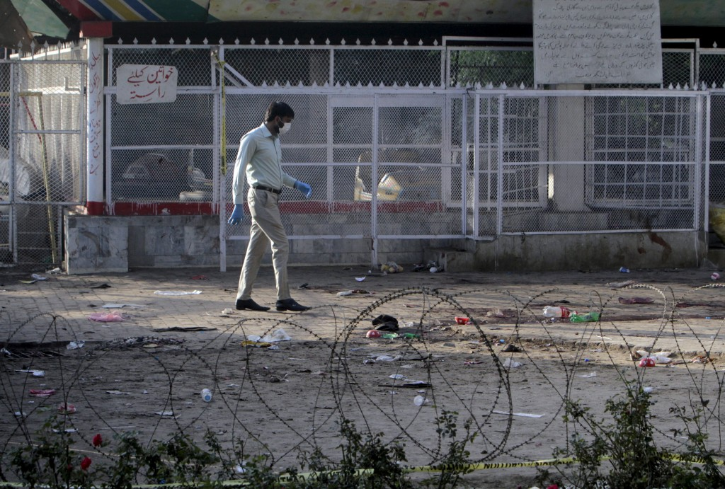 A forensic officer looks for evidence at the site of a blast that happened outside a public park on Sunday, in Lahore, Pakistan, March 28, 2016. REUTERS/Mohsin Raza