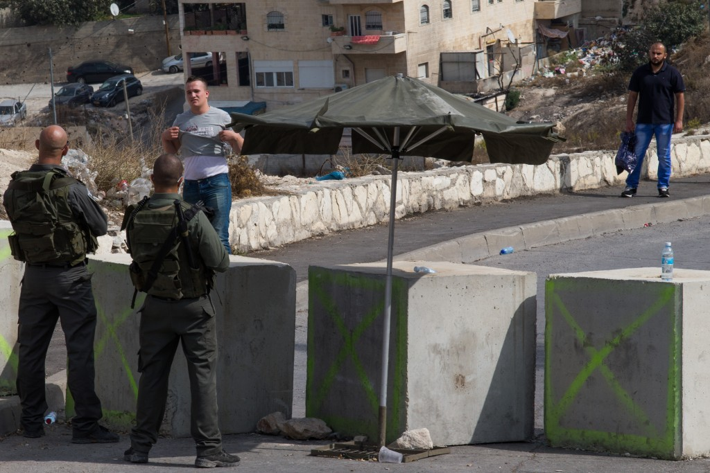 Israeli Border Police   checking Palestinians wanting to pass the entrance to the eastern Yerushalayim neighborhood of Issawiya, on October 20, 2015. (Nati Shohat/Flash90)