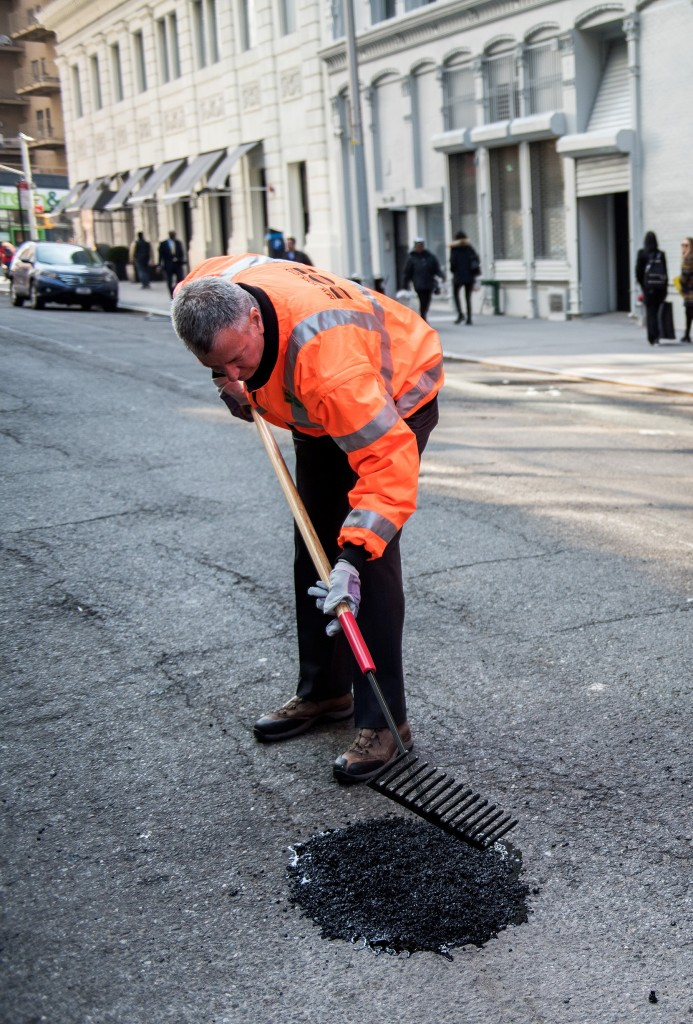 "Mayor Bill de Blasio on Monday fills the ""Millionth Pothole"" in Manhattan. (Demetrius Freeman/Mayoral Photography Office)"