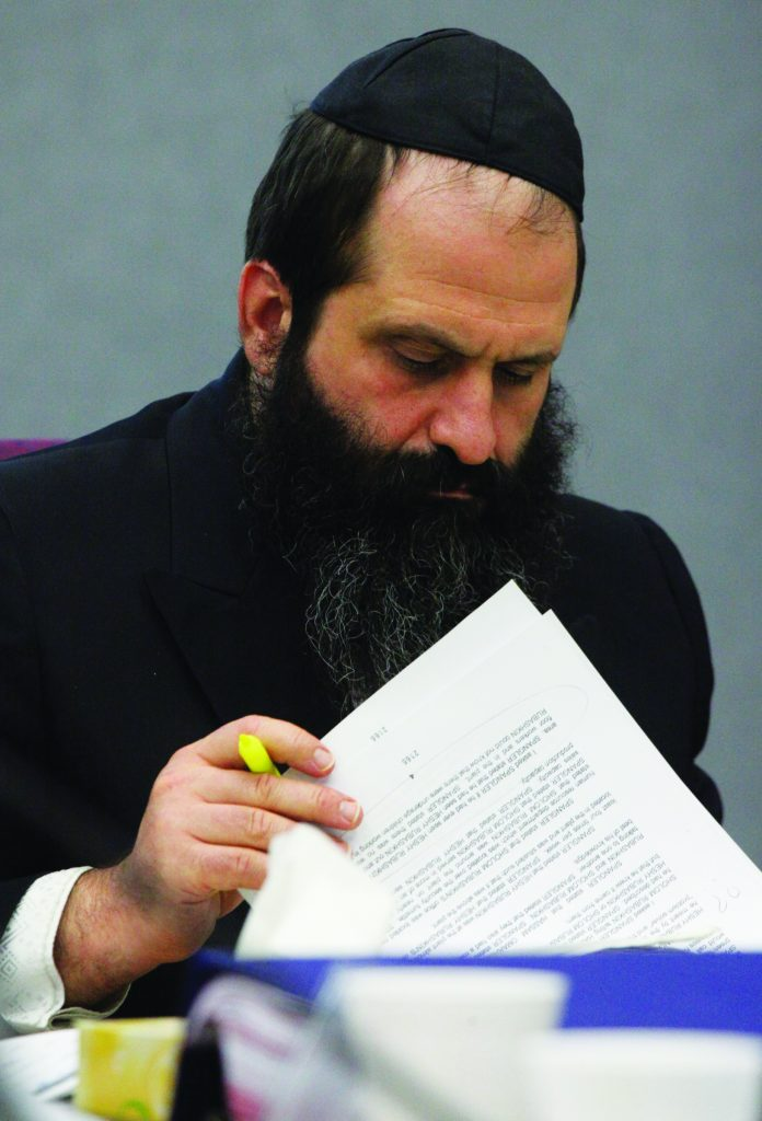 Sholom Rubashkin reads through evidence during his trial on state child labor charges on Friday, May 14, 2010 at the Black Hawk County Courthouse in Waterloo, Iowa. Rubashkin faces 83 counts of child labor violations stemming from a May 2008 immigration raid at the Agriprocessors Inc. kosher meatpacking plant in Postville. (AP Photo/ Andrea Melendez, Pool)