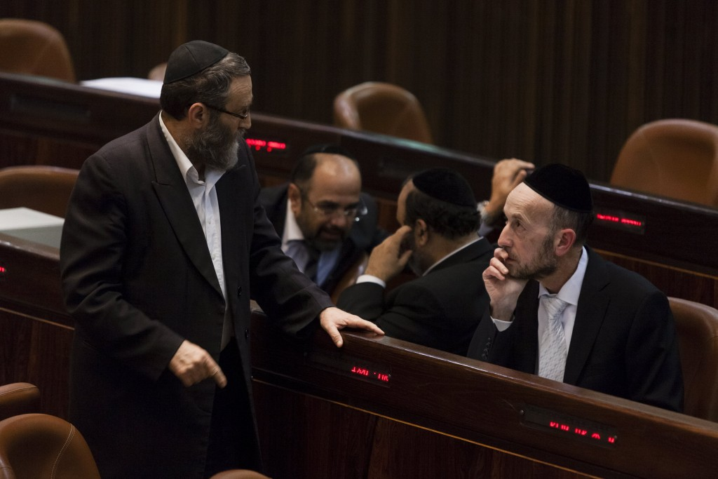 United Torah Judaism MKs Rabbi Moshe Gafni (Left) and Uri Maklev (Right), seen conferring in the Knesset plenum. (Flash90)