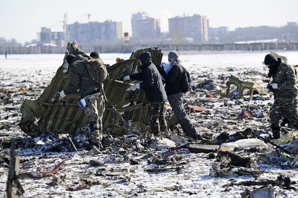Russian Police and Emergency Ministry employees investigate the wreckage of a crashed plane at the Rostov-on-Don airport, about 950 kilometers (600 miles) south of Moscow, Russia, Sunday, March 20, 2016. Winds were gusting before dawn Saturday over the airport in the southern Russian city of Rostov-on-Don when a plane carrying 62 people from a favorite Russian holiday destination decided to abort its landing. (AP Photo)