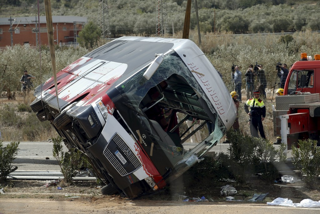 The wreckage of the bus is lifted by a crane after the deadly crash in Freginals, Spain. (Reuters/Albert Gea)