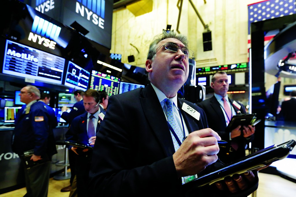 John Bishop, foreground, works with fellow traders on the floor of the New York Stock Exchange, Tuesday, March 1, 2016. U.S. stocks are opening modestly higher as the market recovers from a loss the day before. (AP Photo/Richard Drew)