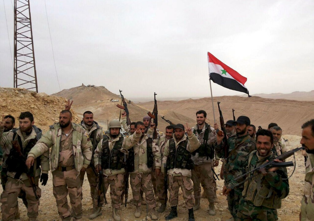 Forces loyal to Syria's President Bashar al-Assad flash victory signs and carry a Syrian national flag on the edge of the historic city of Palmyra in Homs Governorate, in this handout picture provided by SANA on March 26, 2016. REUTERS/SANA/Handout via Reuters ATTENTION EDITORS - THIS PICTURE WAS PROVIDED BY A THIRD PARTY. REUTERS IS UNABLE TO INDEPENDENTLY VERIFY THE AUTHENTICITY, CONTENT, LOCATION OR DATE OF THIS IMAGE. FOR EDITORIAL USE ONLY. NOT FOR SALE FOR MARKETING OR ADVERTISING CAMPAIGNS. THIS PICTURE IS DISTRIBUTED EXACTLY AS RECEIVED BY REUTERS, AS A SERVICE TO CLIENTS
