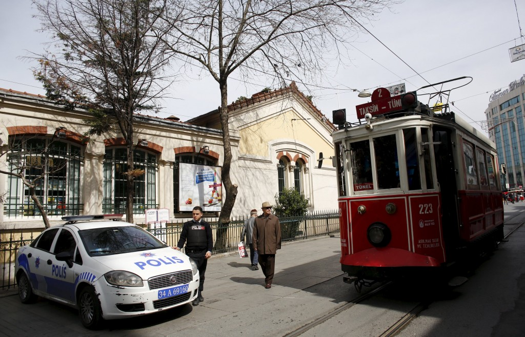 A vintage tram runs along Istiklal street, a major shopping and tourist district, as a Turkish police stands guard in front of the French Consulate in central Istanbul, Turkey March 22, 2016. REUTERS/Murad Sezer