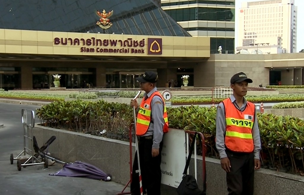 In this image taken from video, security guards stand outside Siam Commercial Bank's headquarters following an accident in Bangkok, Thailand, Monday, March 14, 2016. A number of people died and others were injured at the headquarters of one of Thailand's largest banks when workers accidentally released fire extinguishing chemicals during an upgrade of the building's safety system on Sunday evening, March 13. (Thai PBS via AP Video) THAILAND OUT, TV OUT, NO SALES
