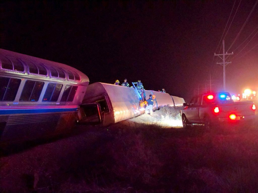 Emergency personnel work on a train that derailed near Dodge City, Kan., early Monday morning. (Daniel Szczerba via AP)