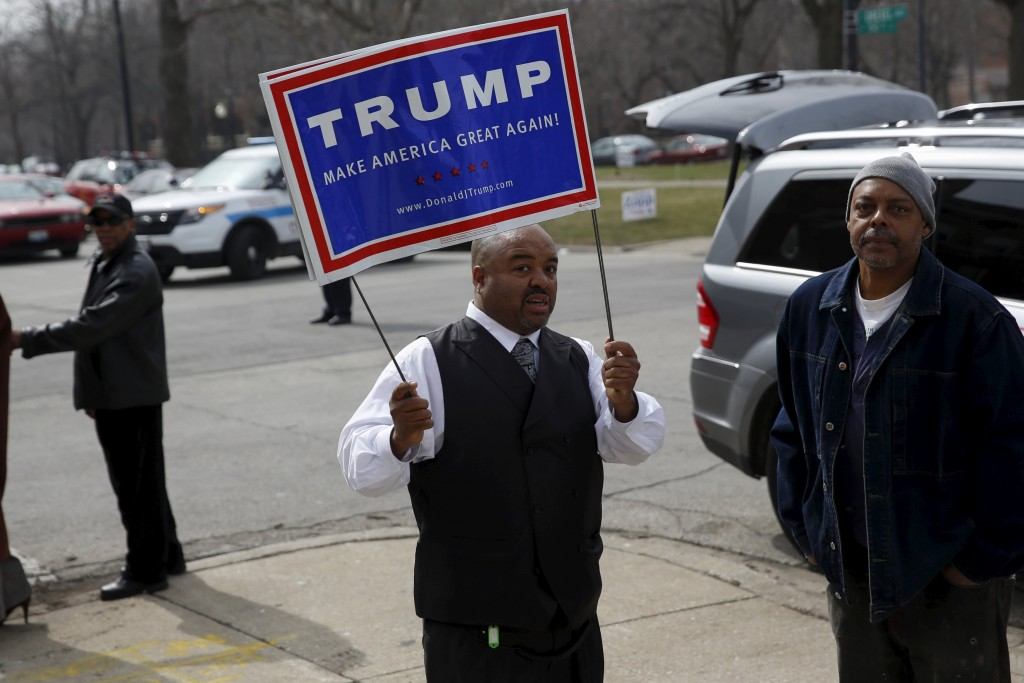 A man holds a sign supporting U.S. Republican presidential candidate Donald Trump outside the Rainbow PUSH coalition where U.S. Democratic presidential candidate Bernie Sanders spoke with Rev. Jesse Jackson in Chicago, Illinois March 12, 2016. REUTERS/Shannon Stapleton