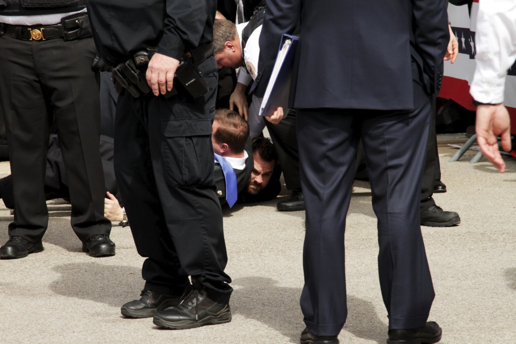 U.S. Secret Service agents detain a man after a disturbance as U.S. Republican presidential candidate Donald Trump spoke at Dayton International Airport in Dayton, Ohio March 12, 2016. REUTERS/William Philpott TPX IMAGES OF THE DAY