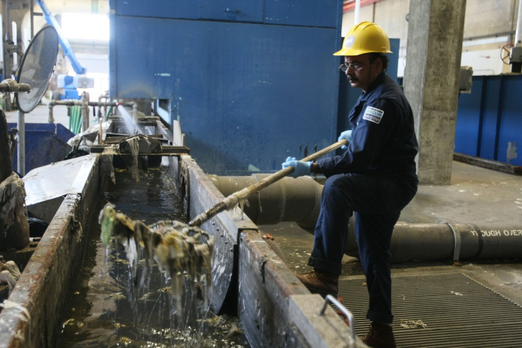 In this 2012 photo taken at the Hyperion sewage treatment plant near LAX, Ameen Uddin removes trash that has been separated from incoming wastewater. (Gary Friedman/Los ANgeles Times/TNS)