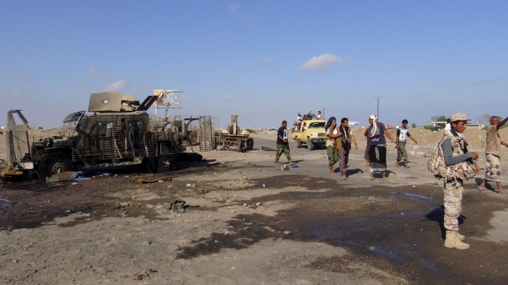Pro-government soldiers and tribal fighters stand at the site of a suicide car bomb attack in Yemen's southern port city of Aden February 29, 2016. A suicide bomber killed four soldiers on Monday when he rammed a car laden with explosives into a military checkpoint in Aden, residents and a security official said. REUTERS/Stringer EDITORIAL USE ONLY. NO RESALES. NO ARCHIVE