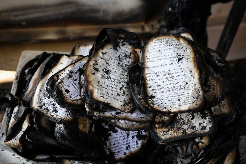 View of burned siddurim inside the synagogue that was set on fire by arsons in CarmeiTzur, February 10, 2016, the synagogue built in memory of three young Jewish boys who were abducted and murdered by Palestinian terrorists in the West Bank last summer. Photo by Gershon Elinson/Flash90