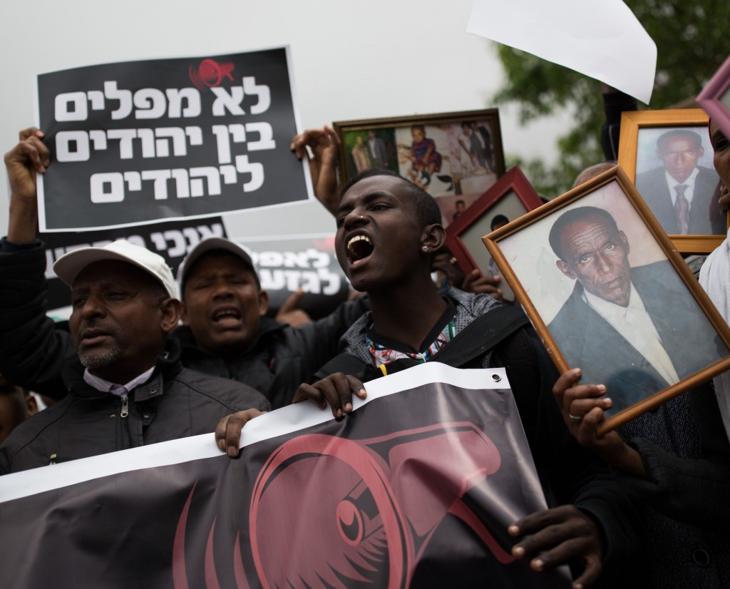 Israelis who immigrated from Ethiopia hold up family photos of loved ones who remain in Ethiopia during a protest to bring the rest of the Falashmura in Jerusalem, on March 20, 2016. Photo by Corinna Kern/Flash90 *** Local Caption *** פלשמורה הפגנה אתיופים אתיופי