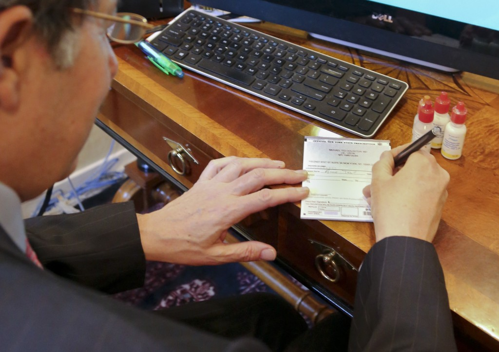 Dr. Michael T. Goldstein, New York County Medical Society President, uses a standard prescription pad, which is being made obsolete by a new electronic-prescription law. (AP Photo/Bebeto Matthews)